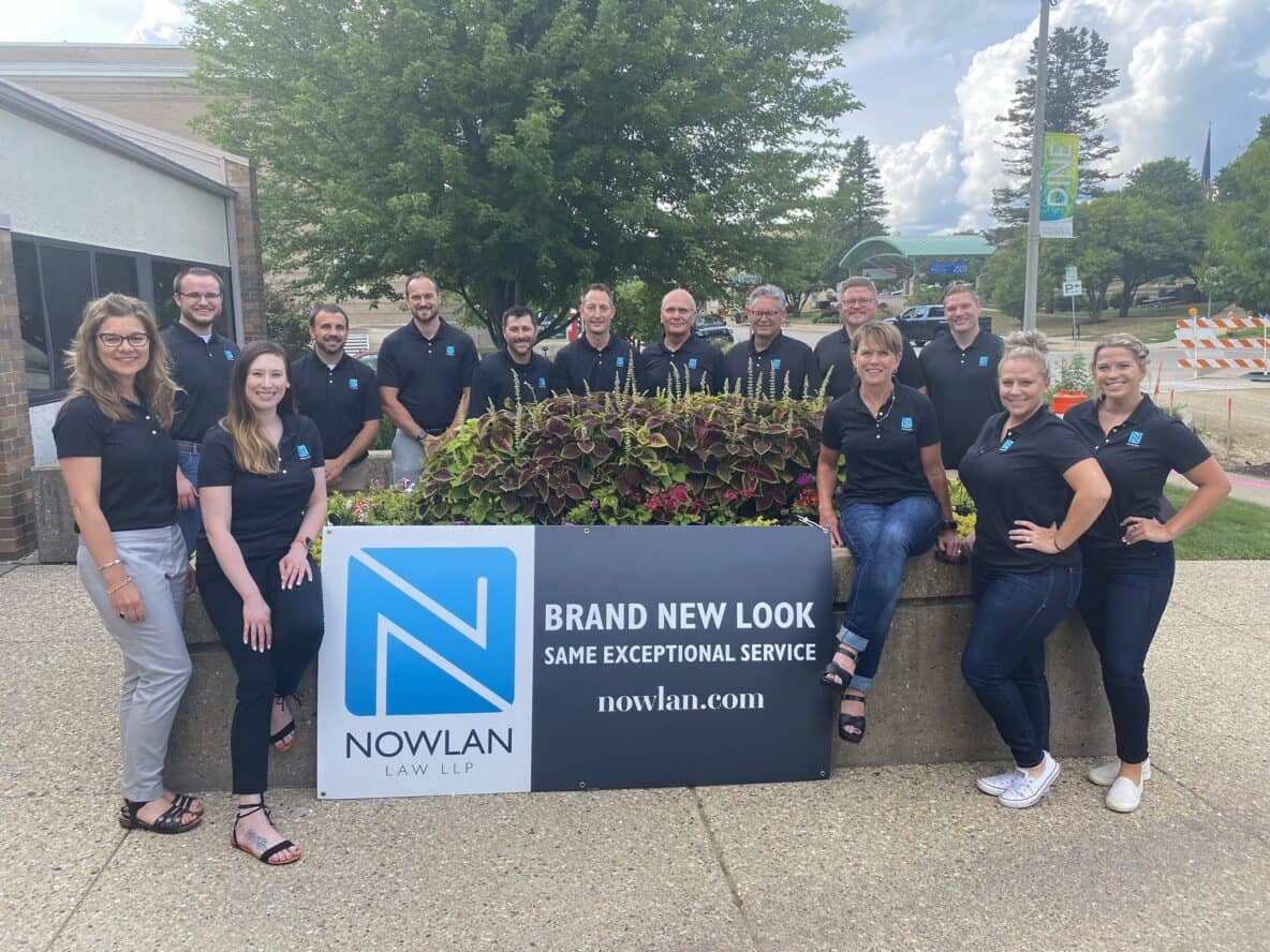 People standing around a sign that says Brand New Look Same Exceptional Service. Nowlan.com